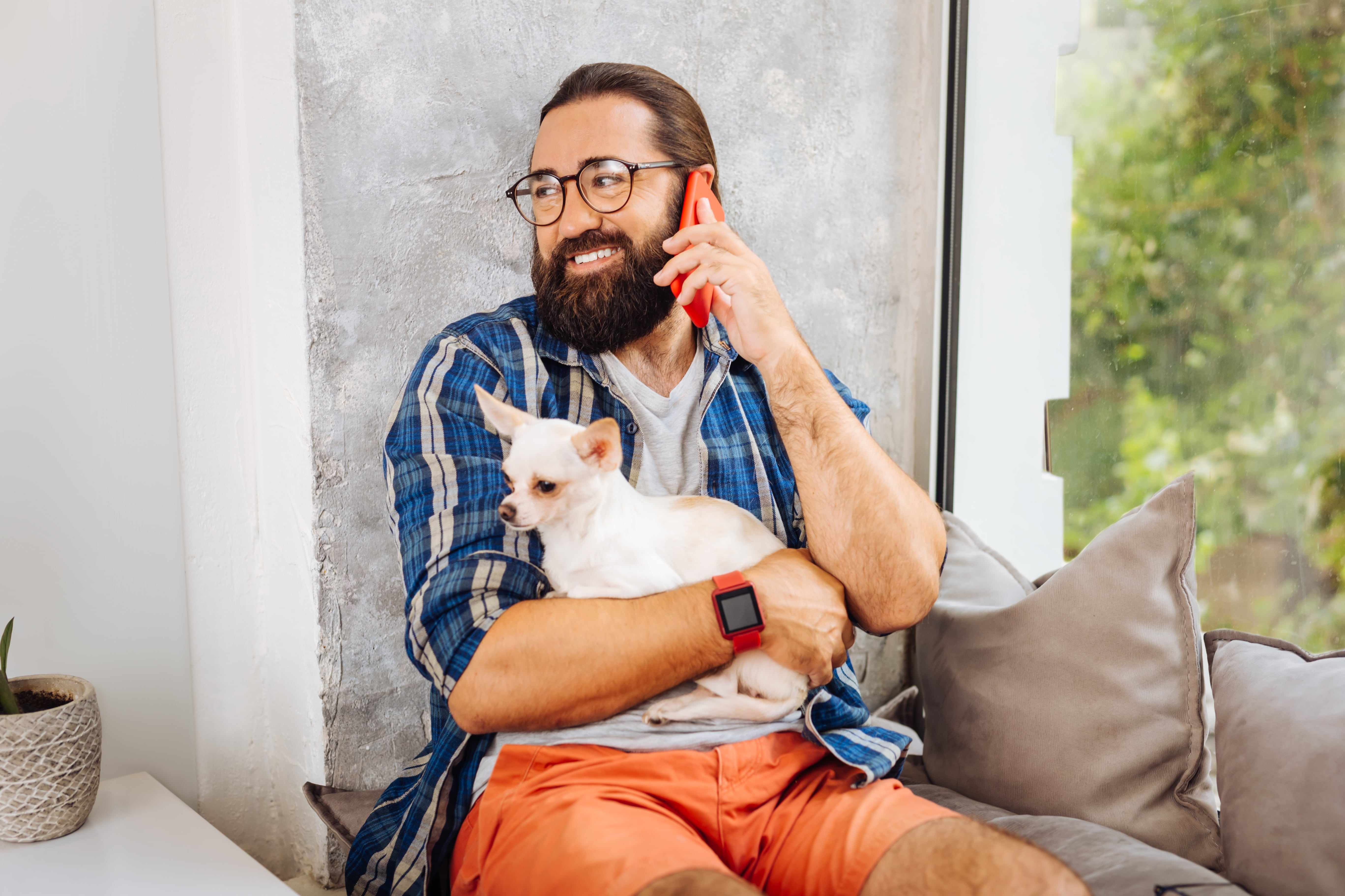 calling-wife-dark-eyed-smiling-man-feeling-cheerful-while-calling-his-wife-while-holding-little-dog-min