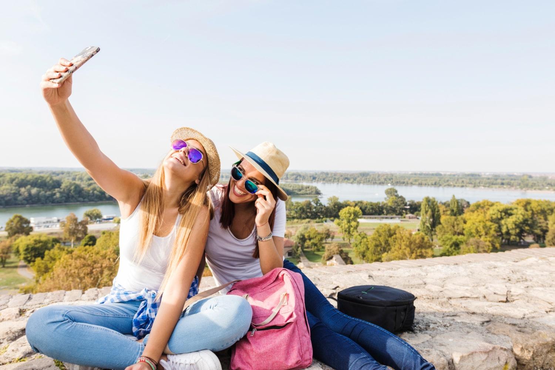 two-happy-female-friends-taking-selfie-on-cellphone-min